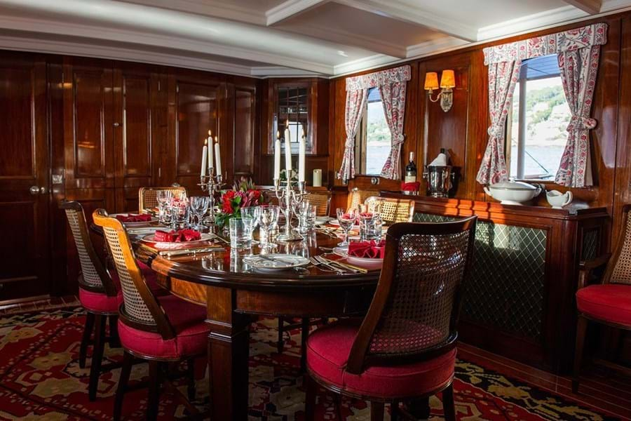 Dine in the mahogany panelled dining room, the beating heart of the yacht